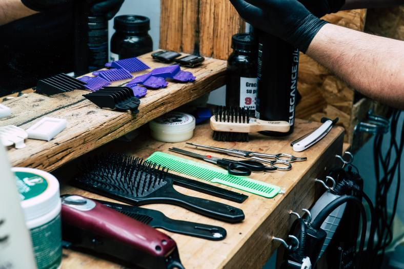 Desk with various barber utilities such as heairbrush, combs, etc.