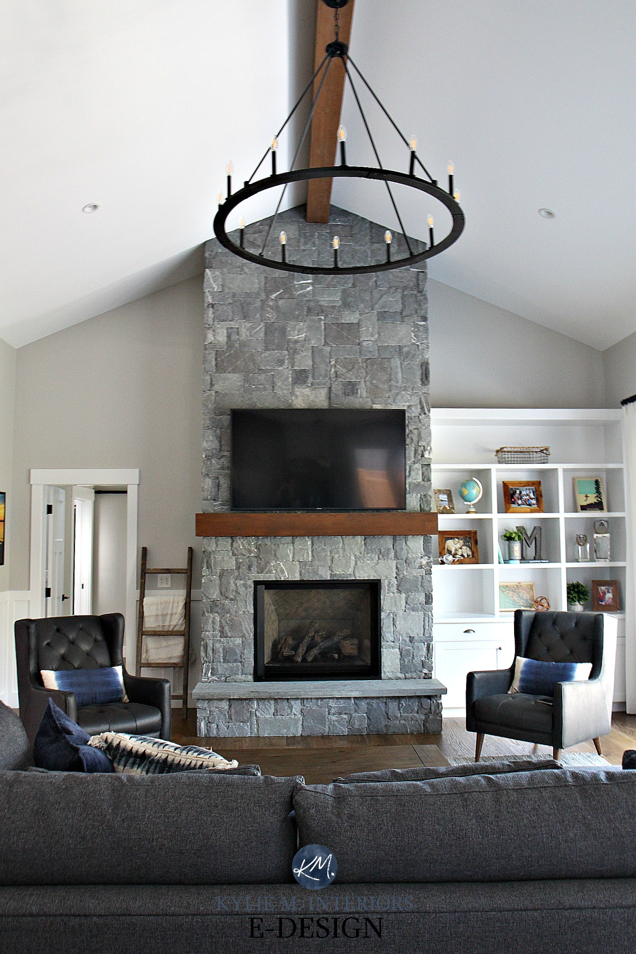 living room design with a stone fireplace and built-in shelves