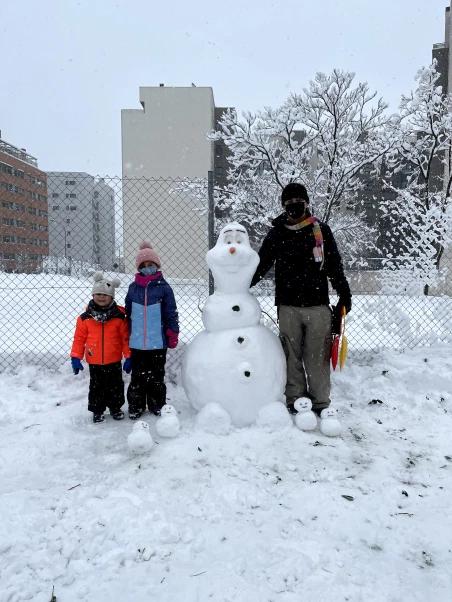 William Viana and family building a snowman