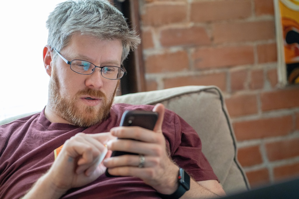Greg Brown looking at his phone on a couch