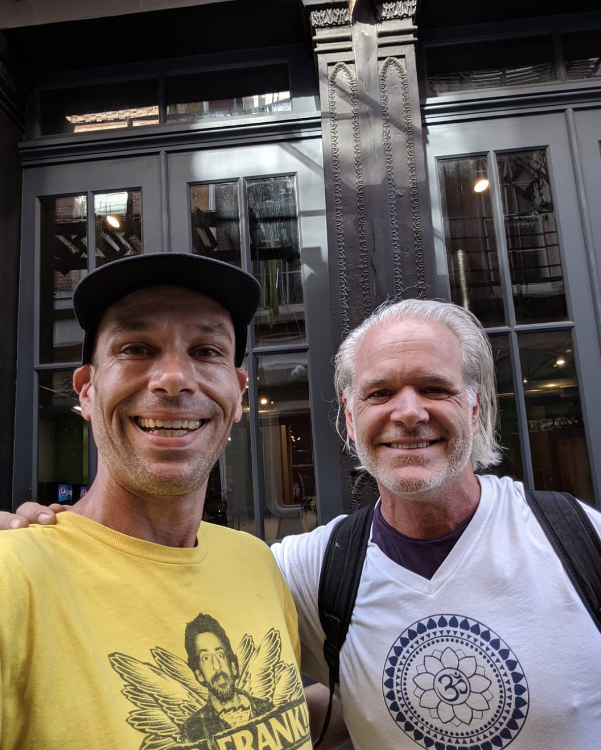 Mark Nordstrom wearing a yellow shirt and standing next to a man in a white shirt